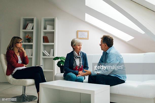 mature couple talking to counselor - patient room stock photos and pictures