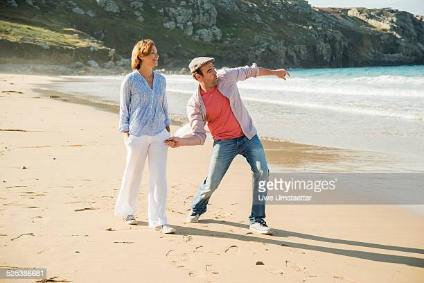Mature couple throwing pebbles out to sea, Camaret-sur-mer, Brittany, France