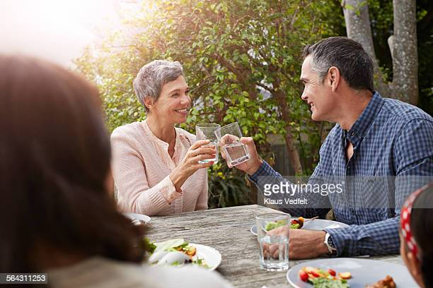 Mature couple toasting at dinner in garden