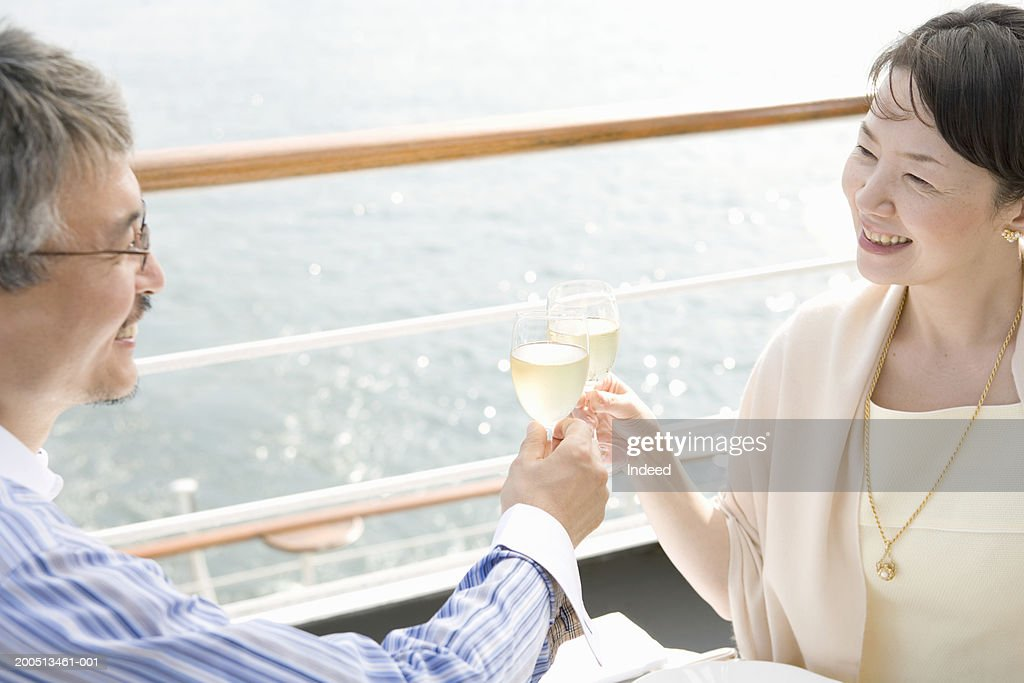 Mature couple toasting on deck of cruise ship, smiling : Stock Photo