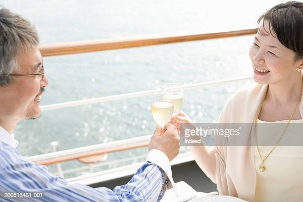 mature couple toasting on deck of cruise ship, smiling - boat deck stock pictures, royalty-free photos & images