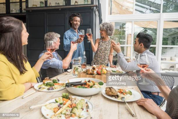 Mature couple toasting wine over dinner with group of friends watching