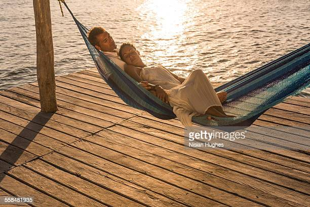 Mature couple together in hammock at sunset