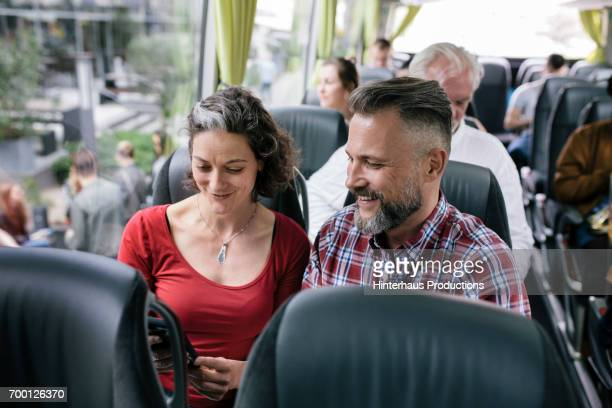 A Mature Couple Travelling On A Bus Check Over Their Route