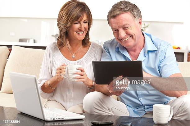 Mature couple using a digital tablet and laptop