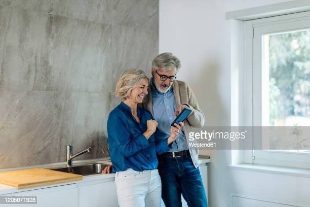 mature couple using cell phone together in kitchen at home - 45 49 years stock pictures, royalty-free photos & images
