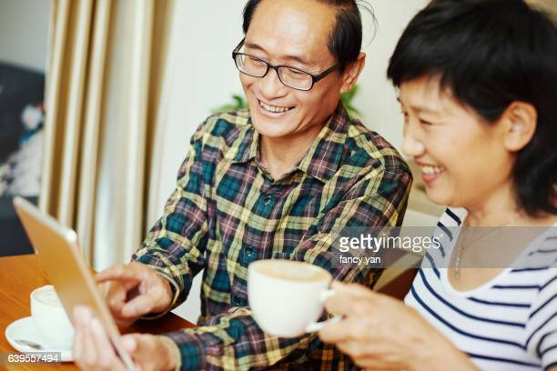 Mature couple using digital tablet at home