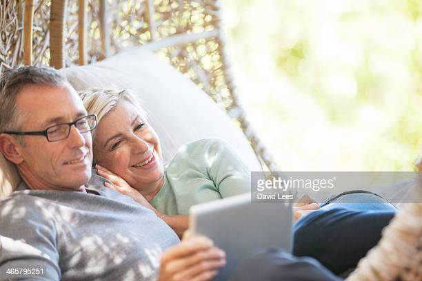 mature couple using digital tablet outdoors - heterosexual couple stock pictures, royalty-free photos & images