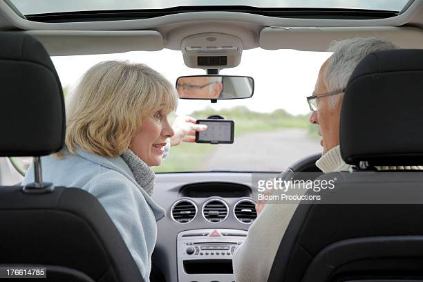 mature couple using in a car using sat nav - driving stock pictures, royalty-free photos & images