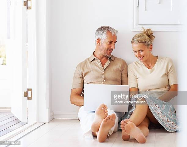 mature couple using laptop at home - mens bare feet stock photos and pictures