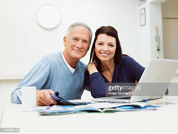 Mature couple using laptop to book vacation