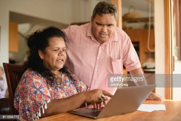 mature couple using laptop with woman pointing - indigenous culture stock pictures, royalty-free photos & images