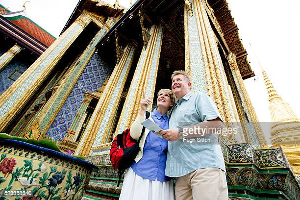 mature couple visiting buddhist temple, bangkok, thailand - hugh sitton stock pictures, royalty-free photos & images