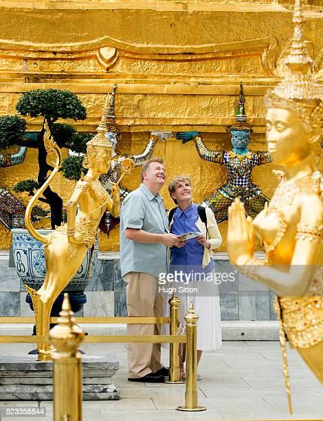 mature couple visiting buddhist temple, bangkok, thailand - hugh sitton stock-fotos und bilder