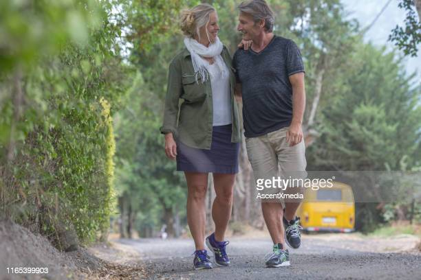 mature couple walk along country road talking - early retirement stock pictures, royalty-free photos & images
