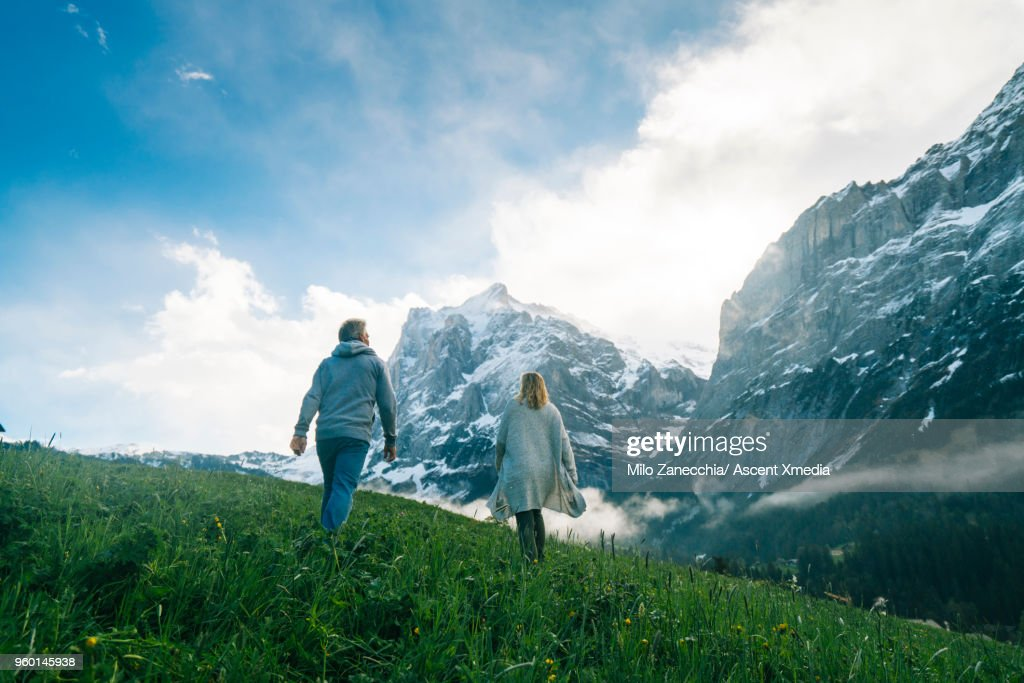 Mature couple walk into meadow, look towards mountains : Stock-Foto