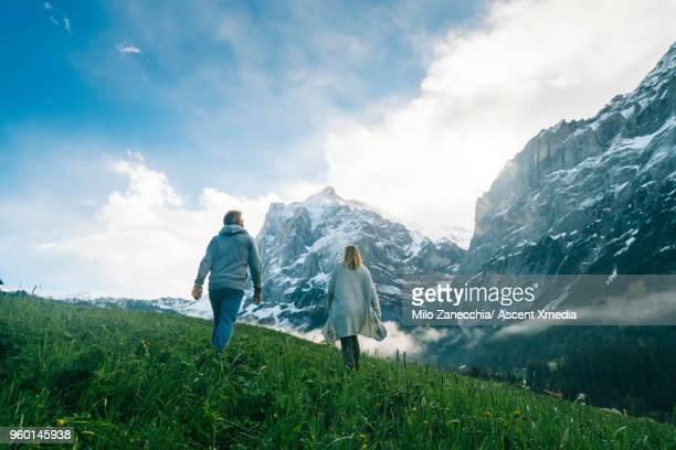 mature couple walk into meadow, look towards mountains - dramatische landschaft stock-fotos und bilder