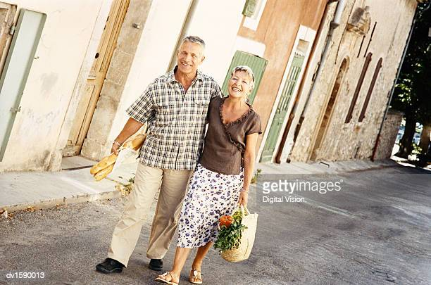 Mature Couple Walk Side by Side Down a Road in Provence Carrying a Baguette and a Basket With Vegetables