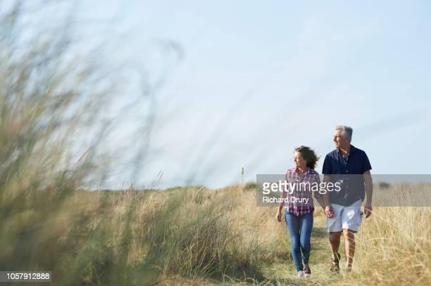 mature couple walking along the coast - esposo fotografías e imágenes de stock