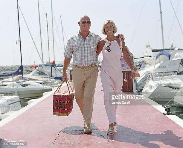 Mature couple walking arm in arm through harbour, portrait