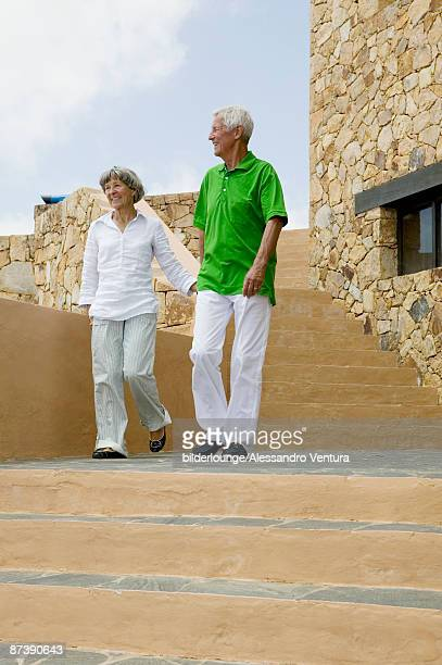mature couple walking down stairs hand in hand