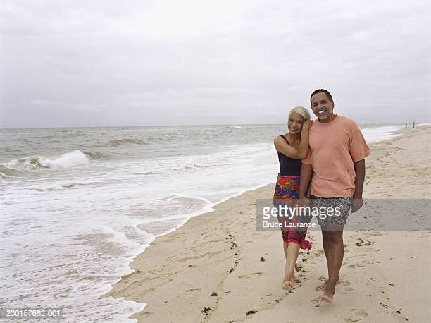 mature couple walking hand in hand at beach - black shorts stock pictures, royalty-free photos & images