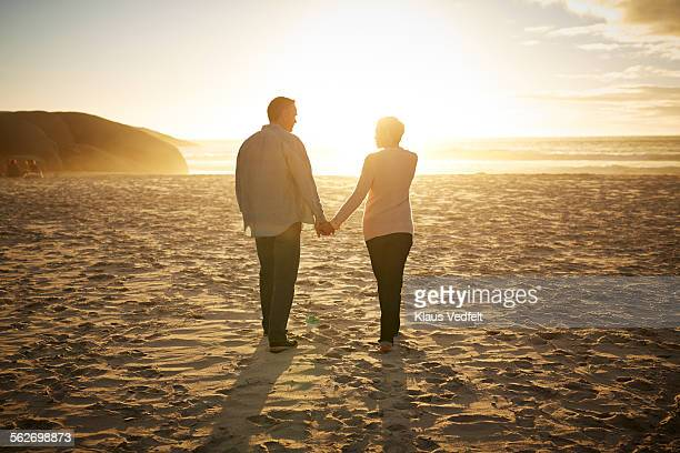 Mature couple walking hand in hand on beach