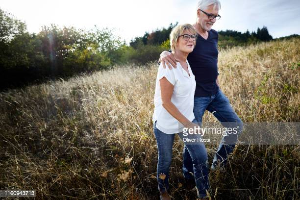 mature couple walking in a field - couple stock-fotos und bilder