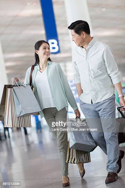 Mature couple walking in airport with shopping bags