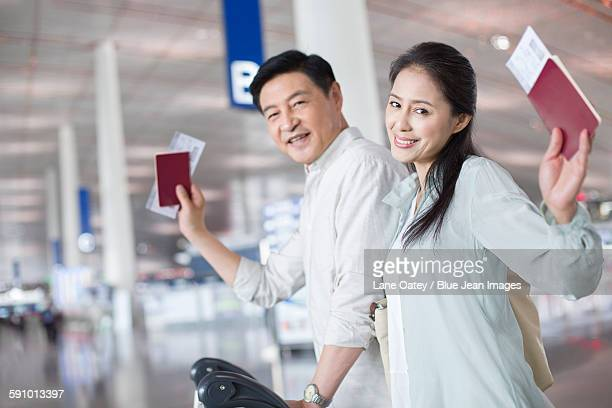 Mature couple walking in airport with suitcase