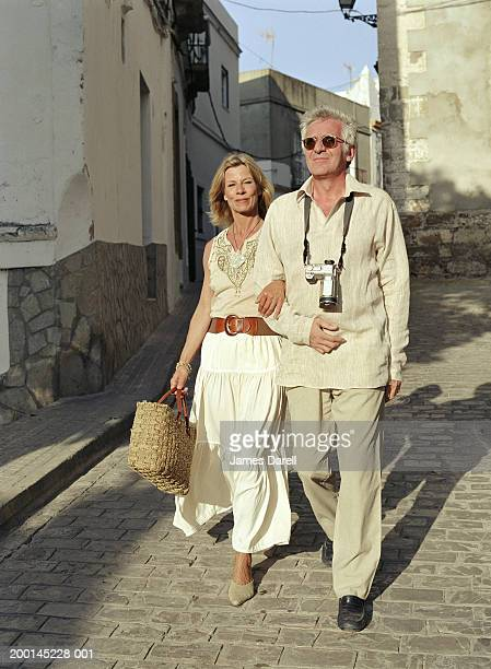 Mature couple walking in street, arms linked, camera around man's neck