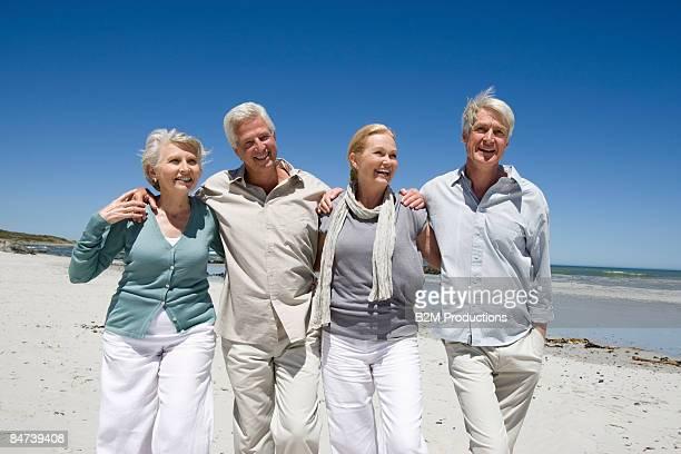 mature couple walking on beach - 55 59 anni foto e immagini stock