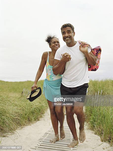 mature couple walking on boardwalk, holding hands - black shorts stock pictures, royalty-free photos & images