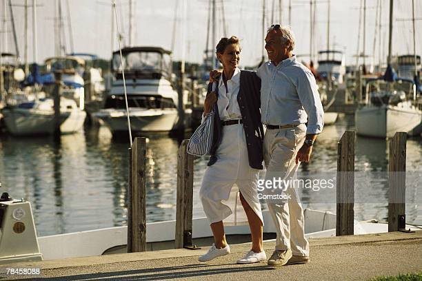 Mature couple walking on dock at marina