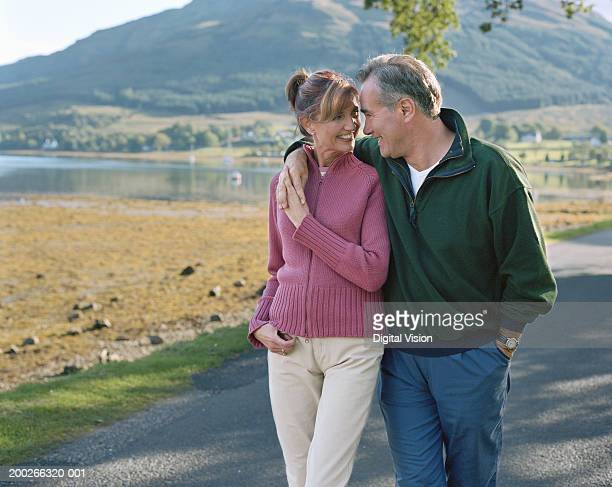 Mature couple walking on path by lake, smiling