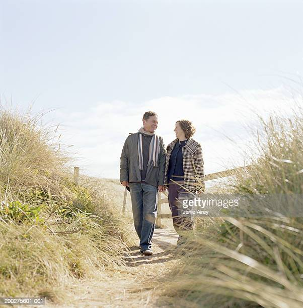 Mature couple walking on path through sand dunes, smiling