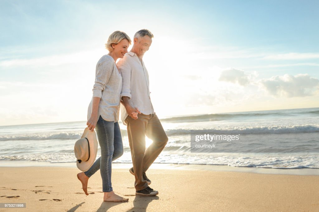 Mature couple walking on the beach at sunset or sunrise. : Stock Photo