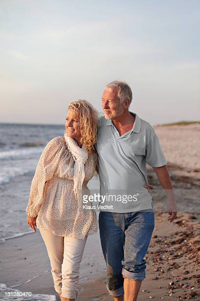 Mature couple walking on the beach in sunset