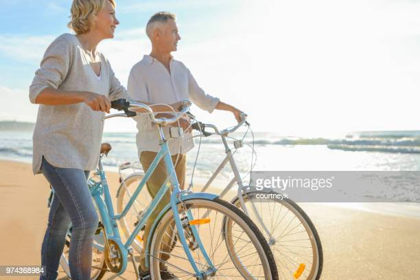 mature couple walking their bicycles along the beach. - baby boomer stock pictures, royalty-free photos & images