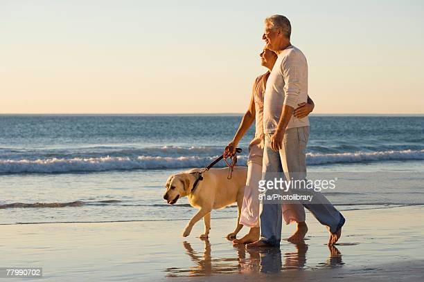 Mature couple walking their dog along the beach