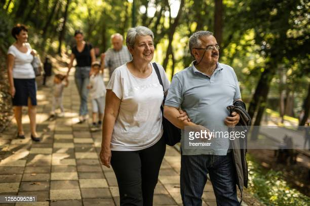 mature couple walking through park on sunny day - arm in arm stock pictures, royalty-free photos & images