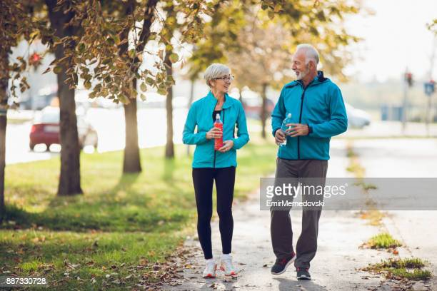 Mature couple walking together with water bottles