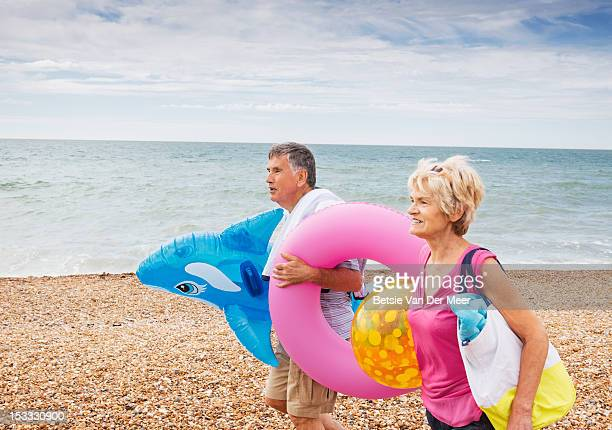 Mature couple walking with beach accessoires.