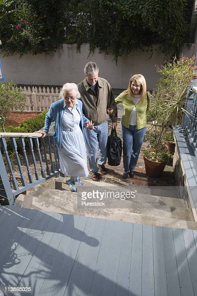 Mature couple walking with senior woman towards front of house