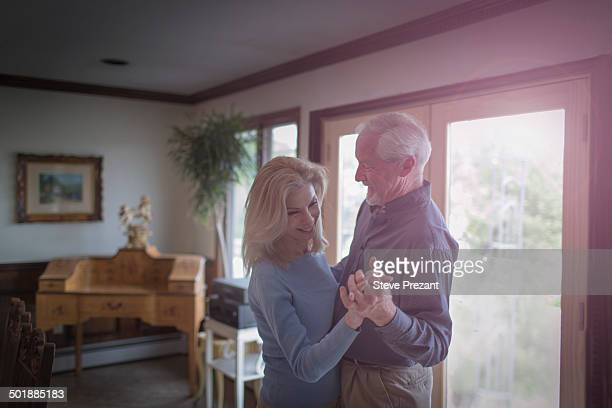 mature couple waltzing together in dining room - gewalt stockfoto's en -beelden