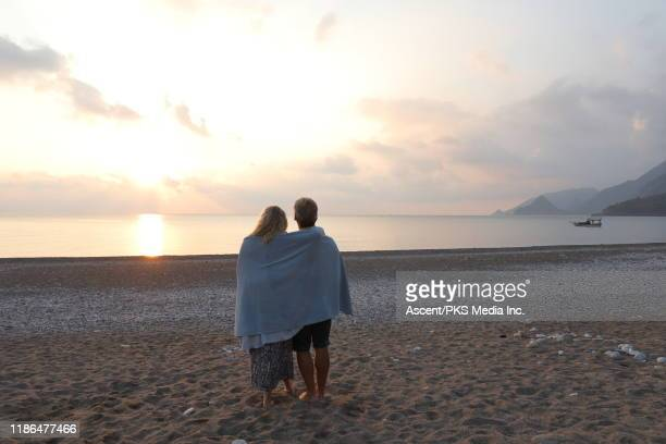 mature couple watch sun rise over sea and mountains - wrapped in a towel stock pictures, royalty-free photos & images