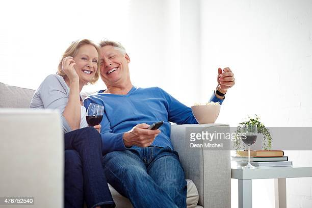 Mature couple watching a comedy show on TV