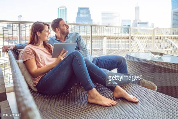 mature couple watching digital tablet on the balcony - izusek stock pictures, royalty-free photos & images