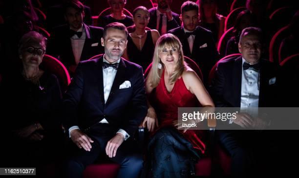 volwassen paar kijken naar film in theater - smoking stockfoto's en -beelden