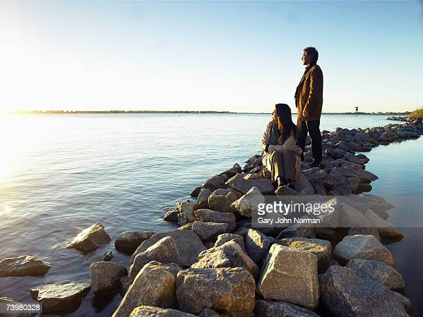 mature couple watching sunrise on rock breakwater - 防波堤 ストックフォトと画像